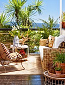 Sunny terrace seating area - wicker sofa and armchair with curved metal frame in front of palm trees and sea view