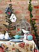 Stylised fruit on plate and china bird in front of birdcage on table against brick wall
