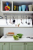 Food preparation on kitchen counter and cooking utensils hanging below wall unit with shelf of vases