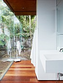 Modern sink in open-plan bathroom area of residential house with view of garden