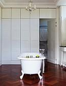Free-standing vintage bathtub on high-quality, dark wood herringbone floor and coffered wooden partition in white bathroom