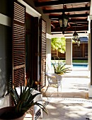 Elegant house with wooden door shutters and encircling porch on pillars in front of pool in garden
