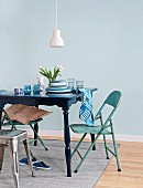 Colour-coordinated accessories on table painted dark blue, turquoise folding chairs and vintage-style industrial metal stool