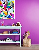 Pale mint-green shelves below painting of colourful triangles on bright purple wall