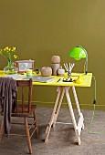 Arbeitsplatz mit Vintage Stuhl zu leuchtend gelber Tischplatte auf Böcken und neongrüner Leuchte, abgerundet durch olivegrünen Hintergrund