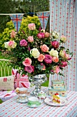 Romantic table setting in the garden with a gorgeous bouquet of roses in a silver chalice from an English tea service and floral table cloth