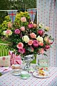 Romantisch gedeckter Tisch im Garten mit prallem Rosenstrauß in silbernem Kelch zu englischem Teeservice und Tischdecke mit Blümchendessin