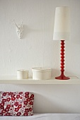 A decorative retro lamp and round boxes on a white shelf