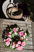 Wreath of roses on garden table, basket on wicker chair