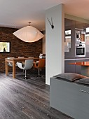 Open-plan living-dining area in architect-designed house with grey fitted kitchen, dark parquet floor and clock hands on white partition