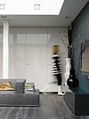 Wohnbereich eines Architektenhauses mit dunklem Parkett und weißen Wandschränken in Hochglanz, auf schwarzem Sideboard stehen große Vasen