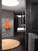 Designer bathroom with floor-to-ceiling, dark pebble mosaic tiled walls and curved wall