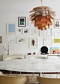 Marbled dining table and shell chairs in front of white sideboard; collection of framed pictures on wall and designer lamp hanging from ceiling above dining table