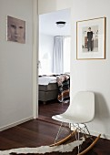 View into bedroom with upholstered bed; white, modern, designer rocking chair on animal-skin rug and photos on white walls in anteroom