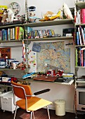 Shelves in boy's bedroom laden with many books and various toys with wooden chair, laptop on desk and map on wall above desk