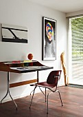 Modern desk and chair below abstract pictures on white wall; wooden sculpture leaning on wall in front of French window with blinds in background