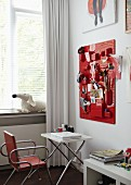 Teenage girl's bedroom with various utensils in containers on red organiser board above laptop on white folding table and metal, upholstered chair in front of window with white curtain