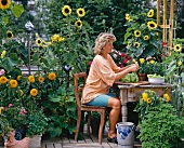 Woman with lettuce on summery terrace