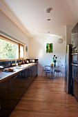 Strip window running parallel to kitchen counter in modern kitchen with pale wooden floor