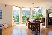 Sunny, spacious dining room with three floor-to-ceiling windows, parquet floor, dining table and solid wooden chairs