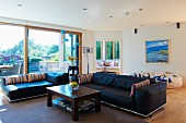 Black leather sofa combination, grey wool rug and simple, wooden coffee table in spacious living room with large window