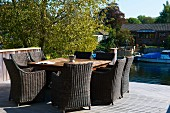 Sunny, wooden deck on river bank with wicker chairs and square table