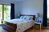 Traditional double bed with floral bed linen in contemporary bedroom with large windows