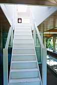 White wooden staircase with balustrades in entrance area of contemporary wooden house