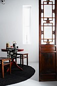 Chinese-style screen next to round tea table set with tea service on black rug