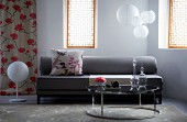 Grey sofa with floral scatter cushion in front of pendant paper lamps; glass carafes on shiny coffee table in foreground