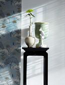 Kleiner Wandtisch mit Vasen neben Wandtapete mit floralem Muster im chinesischen Stil