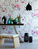 Wallpaper with airy pattern of magnolias; Chinese vases on console table in foreground
