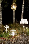 Various lit table lamps and pendant lamp arranged in front of birch trunks in dark woods