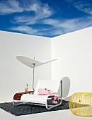 weiße Designer Sonnenliege mit integriertem Sonnenschirm und Abstellfläche auf einer Terrasse