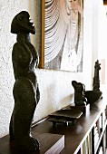 Wooden African sculpture on sideboard-style shelving unit below picture on wall