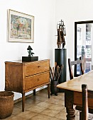 Chest of drawers with tall legs and ethnic objet d'art in contemporary dining room