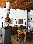 African sculptures, some on pedestals and sideboard, in dining room with wood-beamed ceiling and modern atmosphere