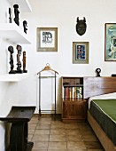 Wooden stool below shelves of African sculptures opposite partially visible bed in corner of bedroom