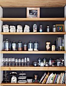 Kitchen utensils on shelving in niche with dark back wall