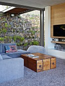 Natürlich belichteter Wohnraum am Hang durch begrünte Gabbionenwand; Vintage Holzkiste als Couchtisch für Sitzgruppe in Grautönen