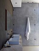 Natursteinwaschtisch mit Aufsatzbecken und Wandarmaturen vor dunkel getönter Wand; Handtuch an Haken in puristischer Sichtbetonwand