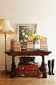 Stacked books and oil painting leaning on wall on top of antique desk above leather suitcases next to Biedermeier standard lamp