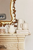 Detail of vintage fire surround with small, white china jugs on mantelpiece and splendid, gilt-framed mirror