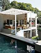 Pool next to contemporary house with roofed terrace in terrain on two levels