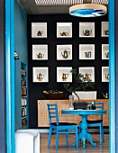 View through open door of blue dining table and chairs in front of black-painted wall with teapots displayed in square niches