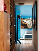 Simple, wooden fitted cupboard in hallway and surrealist picture on blue wall