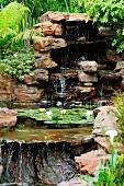 Waterfalls and flowering water lily in pool