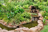 Waterfall and stream formed from boulders in tropical garden
