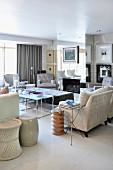 Living room crammed with pale upholstered furniture, tables and mirrored chimney breast