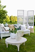 Vases on white side table in front of bench with scatter cushions and screen in garden